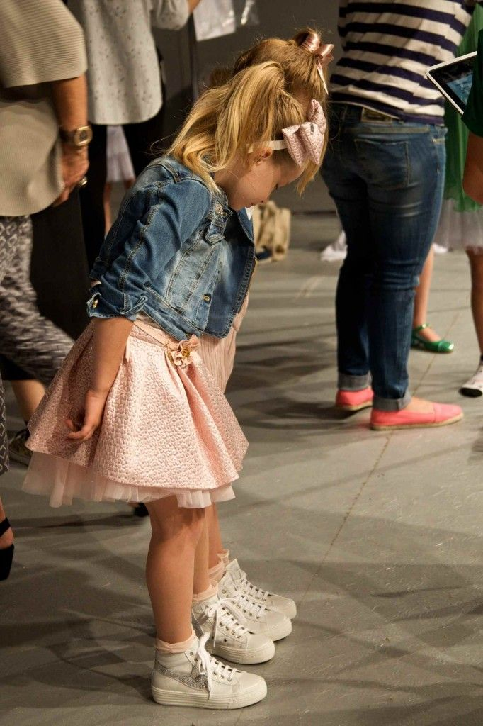 Two young models compare shoes at Miss Blumarine kids fashion show for spring 2014 via @Smudgetikka