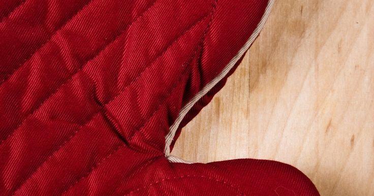 Como fazer luvas de forno. Luvas de forno, também conhecidas como luvas térmicas, são grandes e com revestimento projetado para proteger o usuário do calor. Elas são uma necessidade ao tirar coisas do forno. Fazer suas próprias luvas térmicas, uma única ou o par, é um projeto de costura que não leva mais que uma tarde. O projeto não requer muita experiência em costura.