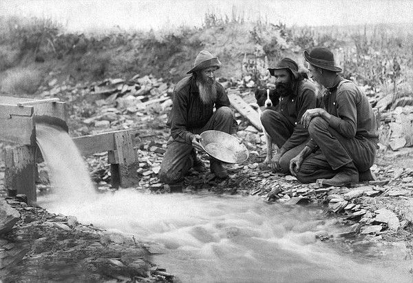 Rockerville, Dakota Territory, 1889. Three gold miners with their dog, panning and washing for gold in a stream.