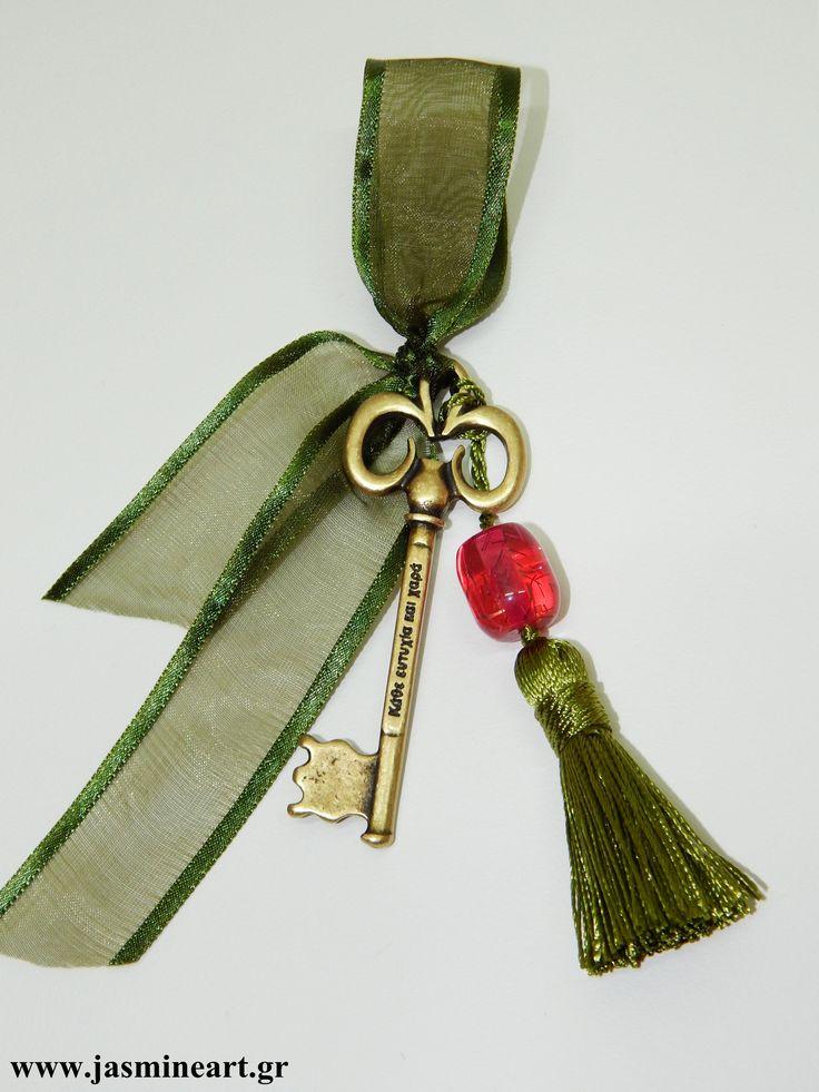 Κλειδί Ευχών  Όμορφο και φινετσάτο γούρι που συνοδεύεται από μπρονζέ  κλειδί ευχών, με μεγάλη κόκκινη χάντρα, φούντα και κορδέλα οργαντίνας. Τιμή:  4.50 €