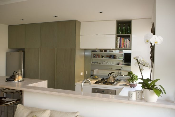 Kitchen uses green stained ply and Corian with mirrored splash back to extend the small living space. Brooke Aitken Design.
