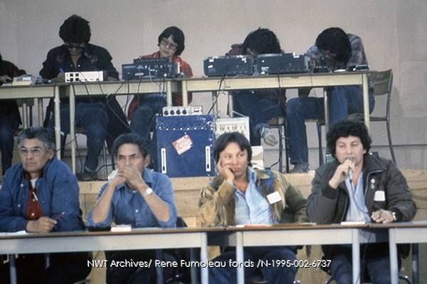 Fort McPherson 08-82- Dene National Assembly - Johnny Charlie, Herbie Norwegian [wearing hide jacket], Georges Erasmus [with microphone]. Charlie Snowshoe, Ruth Carroll.  N-1995-002: 6737 | NWT Archives