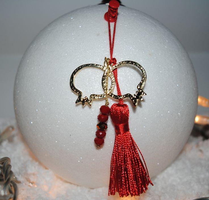Γουράκι με δύο χρυσά ρόδια,χάντρες και φούντα σε γιορτινό κόκκινο χρώμα. 10€