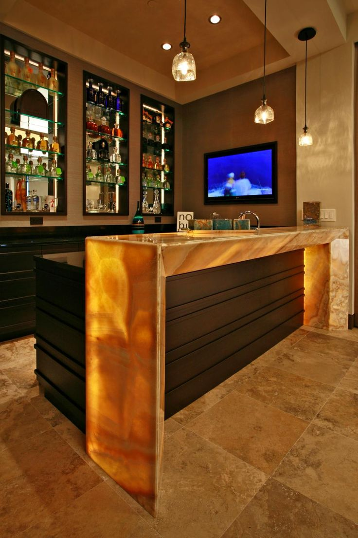 A lighted waterfall countertop frames the outer edge of the bar, creating a unique and attractive accent. Built-in glass shelves stylishly organize bottles and accessories. Tile flooring, a pearly wall panel and dark beige walls blend together for a beautiful finish.