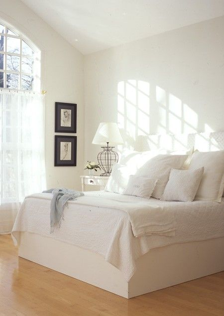 White furniture, wood floors and white bedding modernize a cottage or country bedroom design. While simplicity reigns in this all-white bedroom, luxurious linens and a chenille upholstered headboard add an elegant touch.