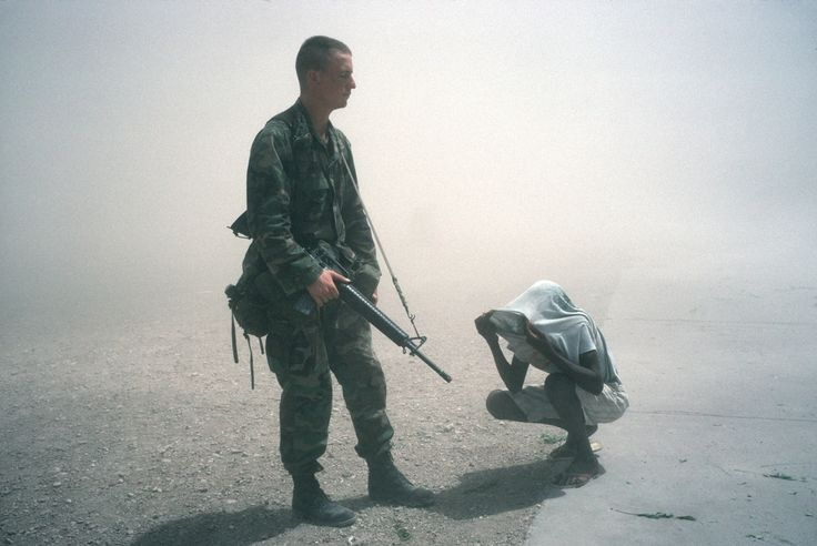 Alex Webb HAITI. Gonaives. 1994. A U.S. soldier and a Haitian teenager are enveloped in dust clouds created by the arrival of U.S. helicopters.