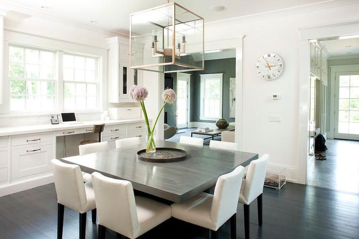 Chic dining room features a 4-light glass and metal lantern illuminating an oversized gray square dining table lined with eight white dining chairs situated across from a built-in desk situated under windows.
