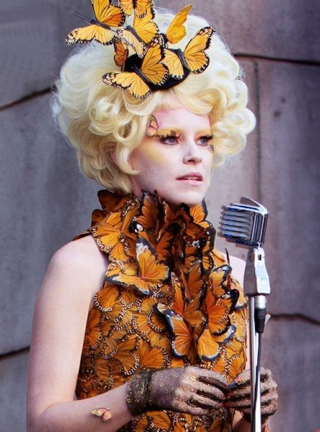 Effie Trinket is the announcer for the Hunger Games and is known for her crazy outfits and her eccentric personality.