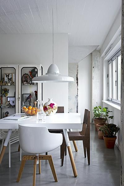 Modern dining table with mixed mid-century chairs, industrial pendant lamp, and display cabinet of curiosities
