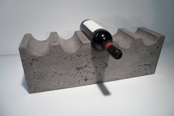 A concrete wine rack, slightly post-industrialist. The safety and reliability of the Wine Rack is queried. Dimensions of wine must be exactly the same as the rack to fit.
