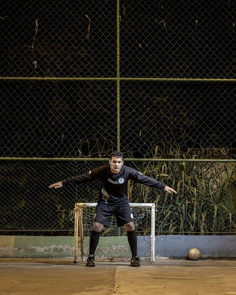 Michael Nascimento, gardien de football, 18ans, devant le goal de son enfance, Favela de Santa Marta, Rio de Janeiro, Brésil, Juin 2014...©Dom Smaz