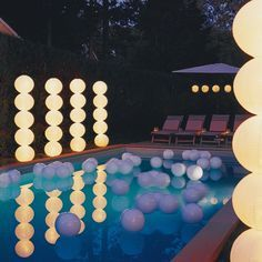"Throw a Glow-in-the-Dark Pool Party: Geometric ""topiaries"" inspired by the paper sculptures of Isamu Noguchi stand on both sides of this swimming pool. A few white plastic beach balls tied to weighted lines float in the pool like pearls cut loose from a giant strand (for safety, never cover the surface of a pool with a large number of balls)."