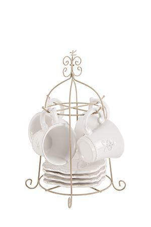 Fleur de lis embossed tea set with beveled edge. Adds a soft, feminine touch to any dining setting. Perfect for everyday use. This classic dolomite tea set includes 4 cups, 4 saucers and stand. Dishwasher and microwave safe.