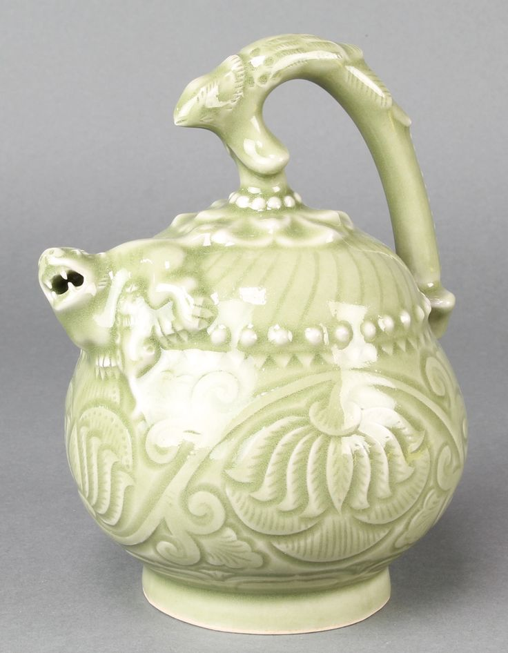 "Lot 118, A Chinese Celadon Mystery puzzle jug, the spout in the form of a Shi Shi with 6 character mark to base 7 1/2"", est £50-75"