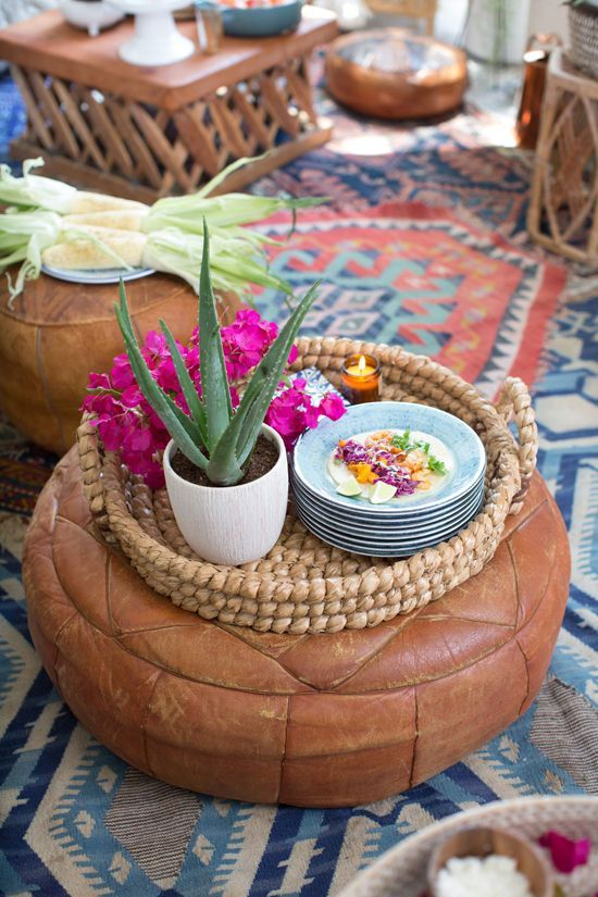 Moroccan leather pouf with a seagrass tray on a woven flatweave rug.