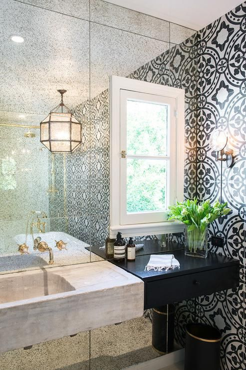 White and black bathroom features an accent wall clad in an antiqued mirror lined with a concrete sink vanity next to black floating vanity drawers.