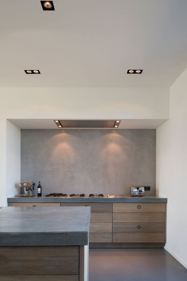 blue grey counter top with grey/umber wood and metal rings as pulls- also black recessed light fittings