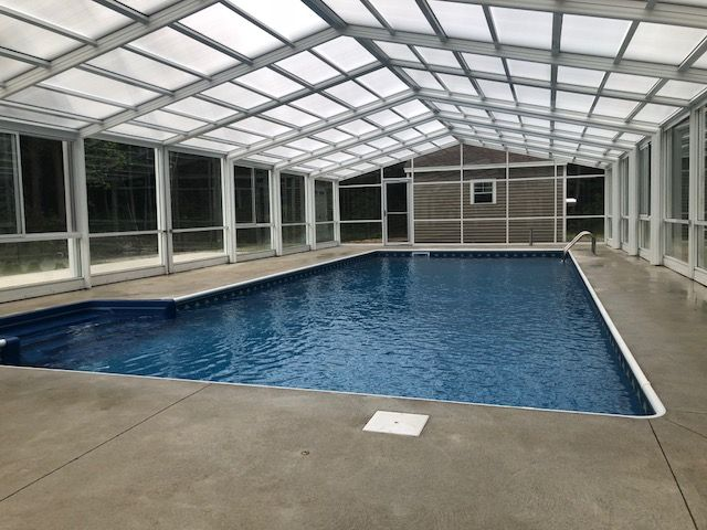This Maine Retractable Pool Enclosure Manufactured Designed By Roll A Cover Gives These Homeowners Year Round Use Of