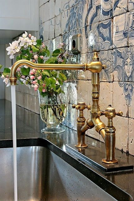 This brass bridge faucet and stainless sink are a beautiful combination for a contemporary home.