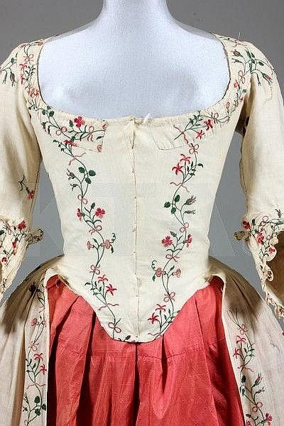 Detail front view, robe à l'Anglaise, c. 1770-1780. Cream lawn delicately embroidered in chain stitch with stripes and sprigs of pinks, convolvulus, dog roses, honeysuckle, tied with pink bows.