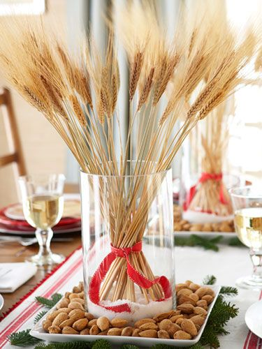 To make this no-fuss natural centerpiece, loosely cinch craft-store wheat stalks with red and white ribbon. Place faux snow inside clear glass vases and nestle stalks on top. Surround with almonds in the shell and evergreen cuttings for easy organic elegance. #christmas #holiday #crafts
