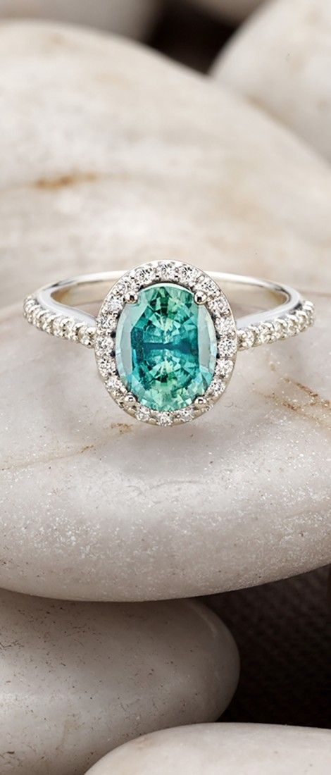 An intricate halo of pavé-set diamonds embraces and accentuates the vibrant gemstone of this brilliant engagement ring.
