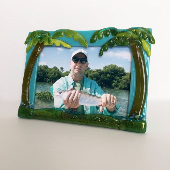 """Style Name: Palm Tree (Double / Aqua) Color: Aqua Frame, Yellow/Green Palm Fronds, Amber Tree Trunk, Iridized Aqua & Amber (water & sand), Dichroic accents. Internal dimensions: Holds photo size 7"""" W x 5"""" H (Landscape) Overall external size approximately: 8"""" W x 6.25 H  This frame is a must have to display treasured vacation memories, or for the tropics lover in your life. These are great for everyone...younger/older...female/male. They make beautiful gifts and look amazing in a grouping…"""