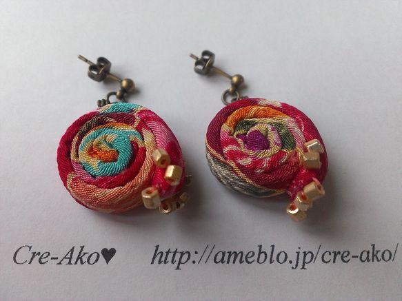くるくる巻いて、ちくちく縫いました。ちりめん紐から生まれたピアス。ピンク&赤をベースに、紫、緑、水色、オレンジなどが混じった色。シンプルにTシャツ&a...|ハンドメイド、手作り、手仕事品の通販・販売・購入ならCreema。