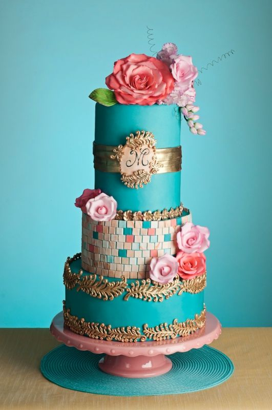 Four-tiered turquoise wedding cake with mainly pink sugar paste flowers .