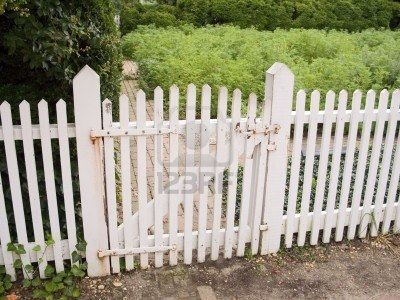 An old white picket fence and garden gate with rounded top edge