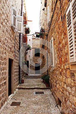 Narrow old pathway with stone buildings in Dubrovnik, Croatia.