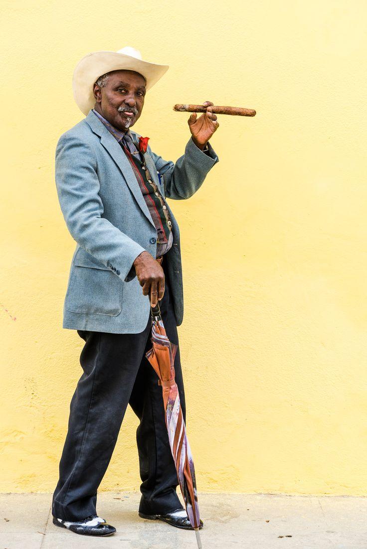 Cuban man smoking big cuban cigar in Havana, Cuba. - Havana, Cuba - September 27, 2015: Traditional Cuban man smoking big cuban cigar on yellow wall background in Havana, Cuba - All About Cuba http://www.Cuba-Junky.com