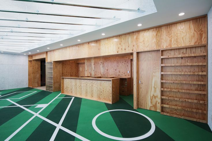 the entire space is designed to evoke the feeling of a ballpark, with striped green flooring and locker rooms situated within the single storey structure.