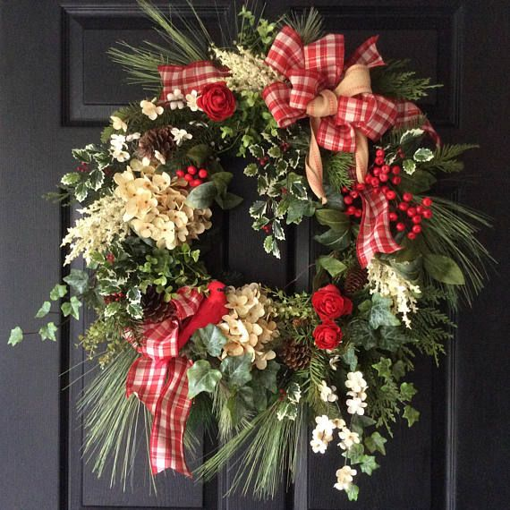Decorate your home with fresh-looking holiday wreath. Cream hydrangeas, astilbe, red ranunculus, pine cones and gorgeous red berries stand out against the evergreen, holly and ivy wreath. A lush double bow of red and beige plaid and red-striped ribbon adds a bright and cheery note to