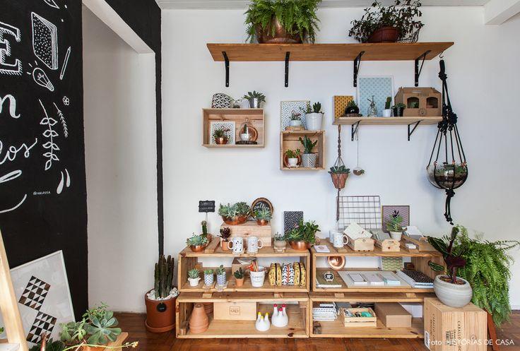 Caixotes de madeira e prateleiras expõem vasos com suculentas e artigos de papelaria.