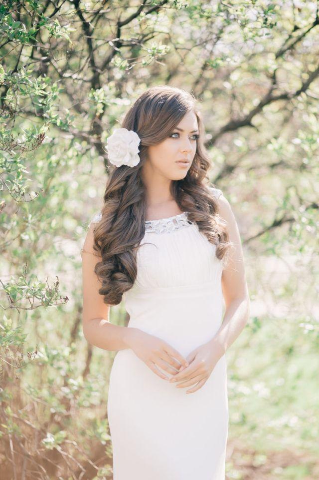 vagues molles et fleur blanche dans les cheveux d'une jeune mariée