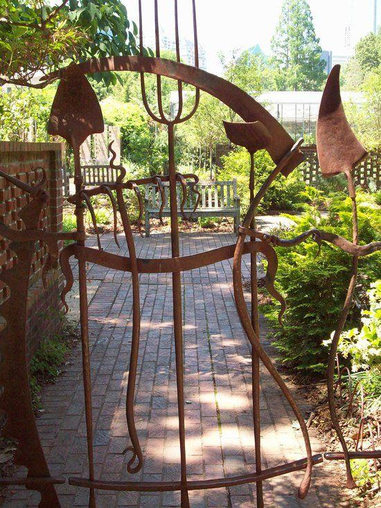 Ferramentas de jardinagem em portão de metal, de aspecto enferrujado, na entrada do jardim.  http://www.architectureartdesigns.com/20-beautiful-garden-gate-ideas/