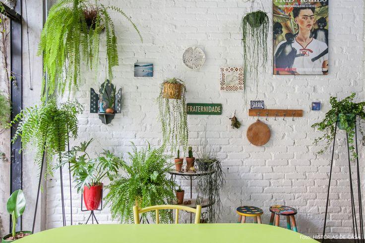 Parede de tijolinho pintado de branco, muitas plantas e galeria com quadros e objetos.