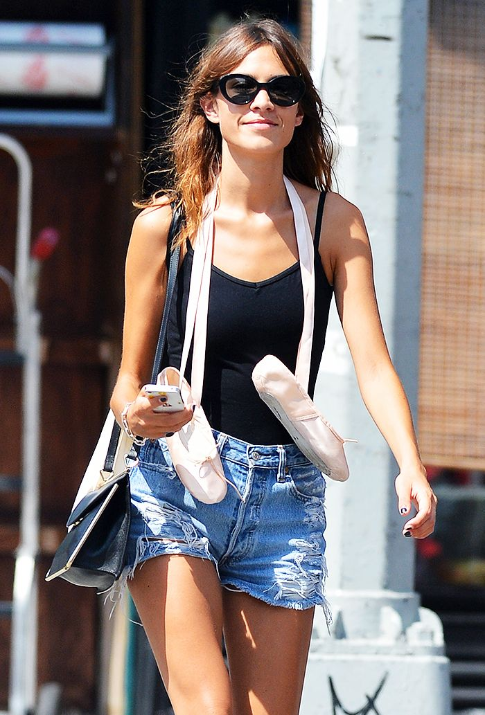 Alexa Chung exiting a ballet class wearing denim cutoffs over a black leotard with ballet clippers swung around her neck