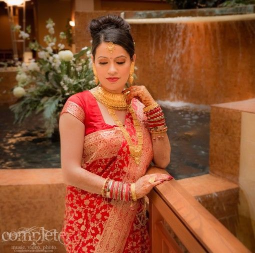 Nepali bride in red and gold sari with two layers of gold necklaces and earrings and tikka