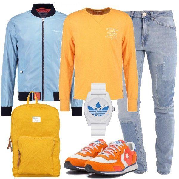 Il bomber azzurro cielo all'interno è arancione. Sopra ai jeans slim fit chiari effetto usato troviamo la maglietta a manica lunga gialla con scritte stampate. Al polso l'orologio bianco con logo azzurro, ai piedi le sneakers basse che riprendono tutti i colori dell'outfit. Zaino giallo con scomparto per pc in spalla.