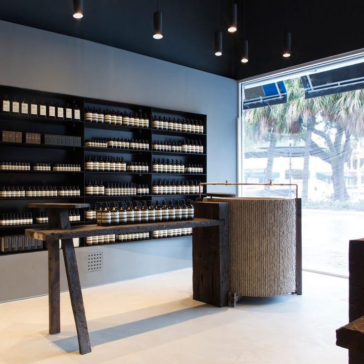 Aesop store - black ceiling with black ceiling pendants - black wall cabinet - open shelving - neutral colour palette