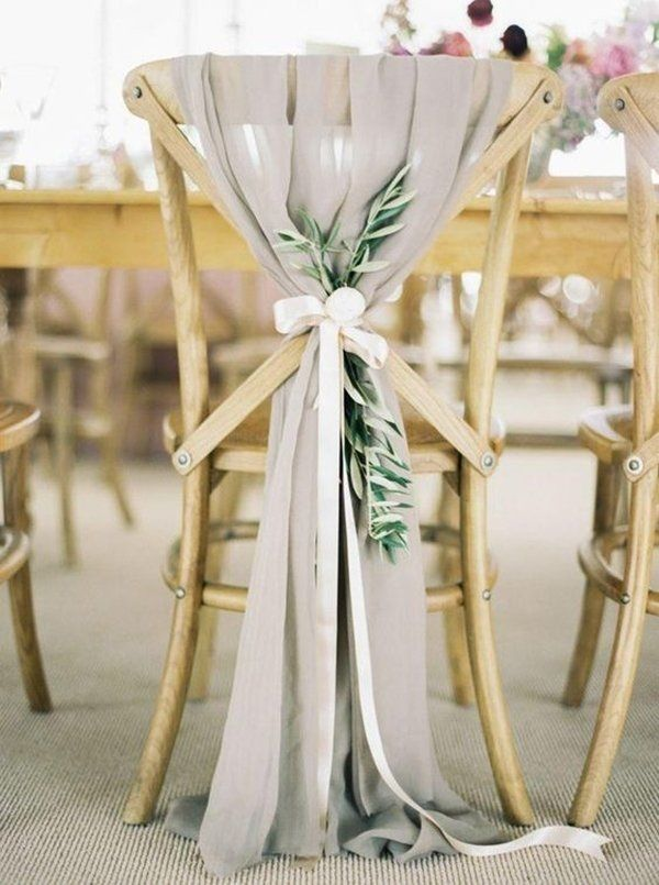 Loving the way this lightweight chiffon fabric is draped over the chair and tied off with long white ribbon and sprigs of greenery! What a unique chair tie idea!
