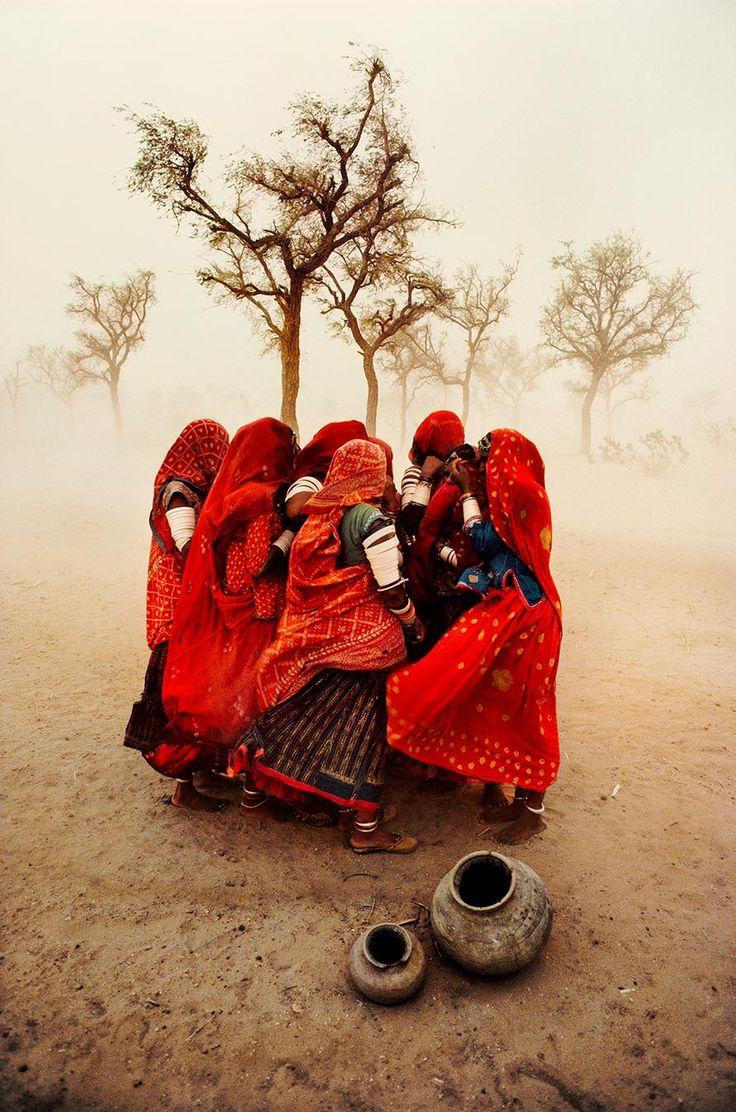 Dust Storm, India. Photograph by Steve McCurry. Beautiful scene. Women huddled together against the wind wearing billowing, scarlet red dresses.
