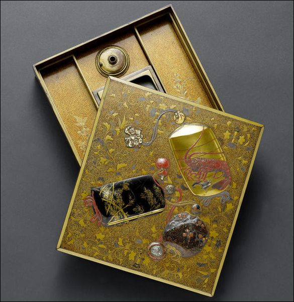 A gold lacquer suzuribako and cover Late Edo Period. Bearing a rich nashiji ground and decorated in Haritsu style with two inro and a tonkotsu with corresponding ojime and netsuke applied in high relief set against a ground of trailing foliage, the interior of the lid lacquered in gold takamakie with chrysanthemums growing from behind a bamboo fence on a nashji ground, with suzuri and gilt mizuire and two removable trays, unsigned, with wood storage box.