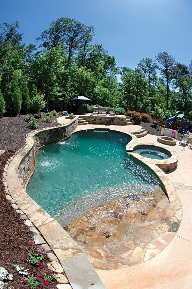 Concrete pool with an 8' round spa and many rock features including an exposed beam wall,rock steps and retaining wall.
