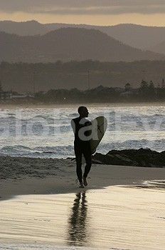Silhouette of lone male surfer on beach against sunset. A lone male surfer walks along the beach holding a surfboard silhouetted against a golden sunset.Stock Photo By Leon   O'Neil