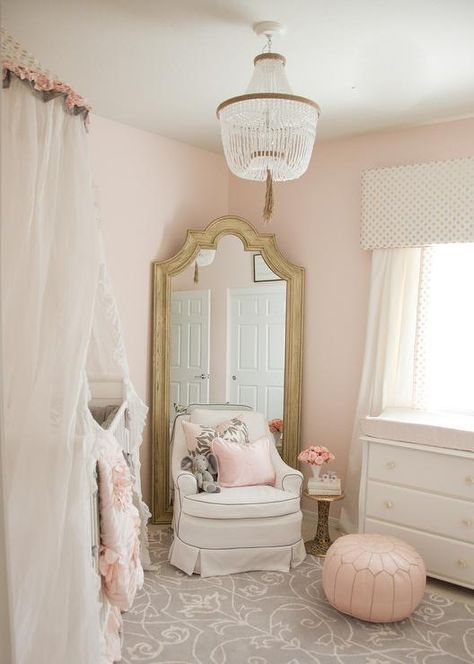 A PB Kids Rissa crystal beaded chandelier illuminates a whimsical pink and gray girl's nursery design featuring a white crib accented with a stunning sheer white canopy while a white skirted glider with gray piping sits on a gray and white area rug in front of a gold French nursery floor mirror positioned caddy corner against light pink walls. Beside the glider, a gold pedestal side table is placed behind a pink Moroccan leather pouf sat in front of a white dresser boasting a light pink chan