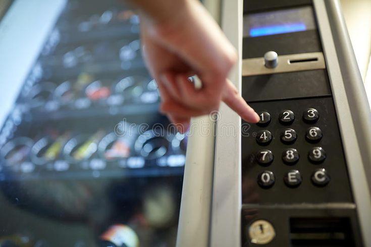 Hand pushing button on vending machine keyboard sell