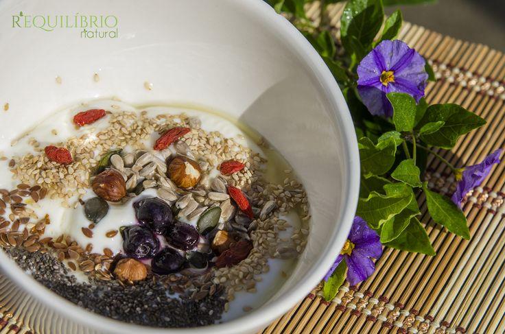 Bom dia!  Iogurte natural com sementes de chia, linhaça, sésamo, abóbora e girassol; bagas goji, mirtilos, avelãs; geleia de agave.